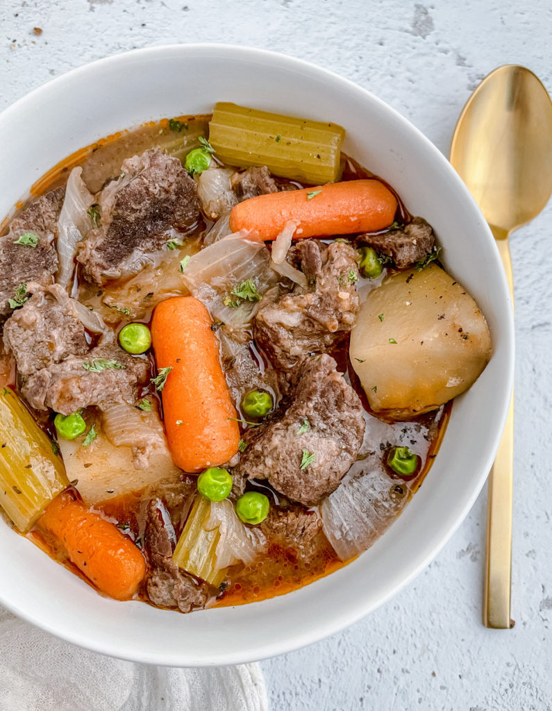 Bowl of Instant Pot Chunky Beef Stew with a spoon on the side