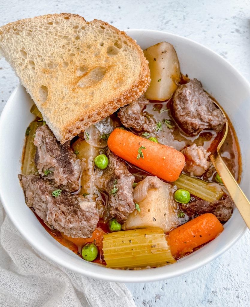 Bowl of Instant Pot Chunky Beef Stew with sourdough bread and a spoon